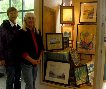 Sue Ellingsen and Gail Ringwood celebrate putting the finishing touches on their Credit Union exhibit.