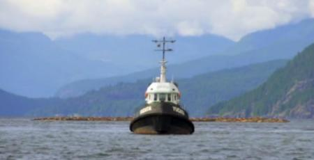 Tug pulls log boom past visitors during July